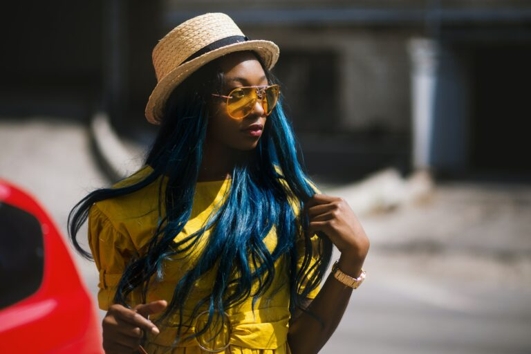 A beautiful woman with blue hair wearing a weave hat walking